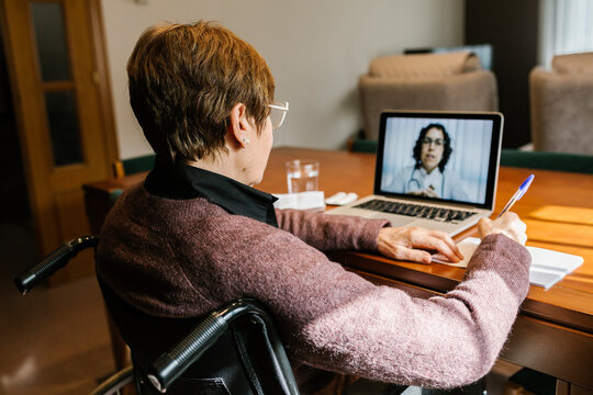 Senior woman sitting on wheelchair writing in book while video consultation at home during COVID-19