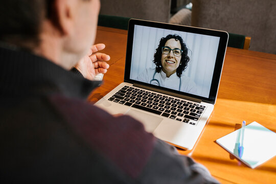 Smiling female doctor on video call consultation with senior male patient at home Covid-19