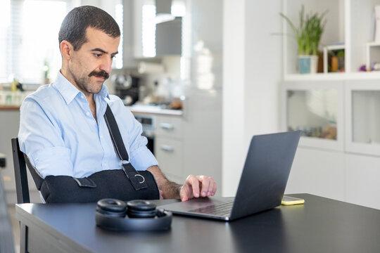 Man wearing arm sling working on laptop at home