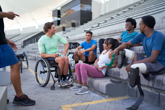 Diverse young athletes talking in stadium bleachers
