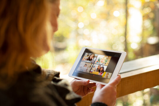 Woman video chatting with family on digital tablet screen