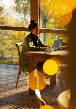 Small business owner working at laptop in sunny autumn cafe