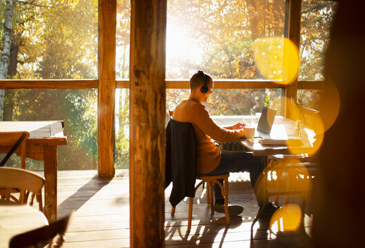 Businessman with headphones working at laptop in sunny cafe