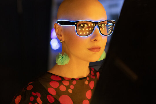 Portrait stylish woman in neon glasses and earrings