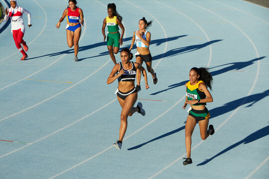 Female track and field athletes running on sunny track