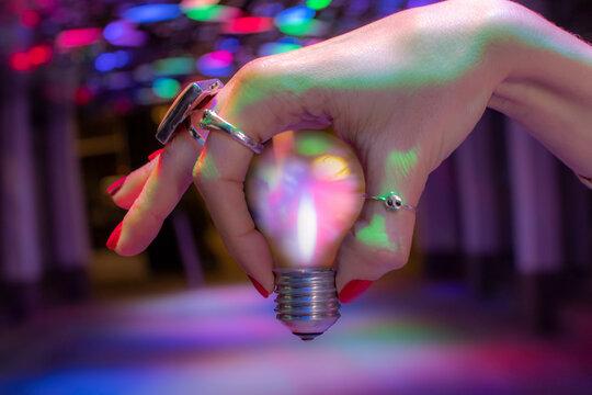 Close up hand holding light bulb under neon light