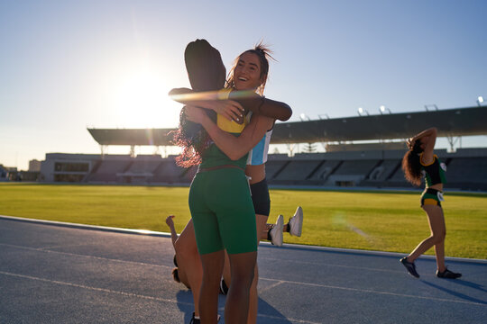 Happy female track and field athletes hugging on sunny track