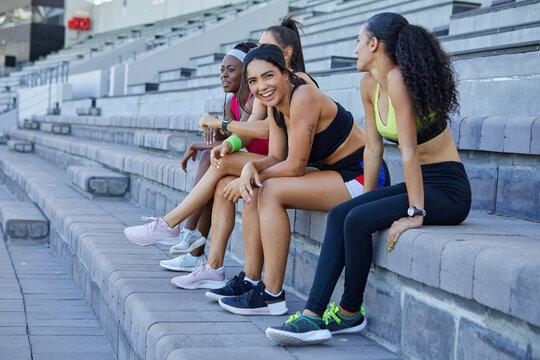 Female track and field athletes taking a break on stadium steps
