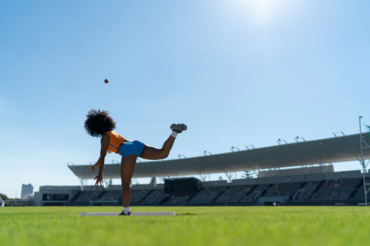 Female track and field athlete throwing shot put in sunny stadium