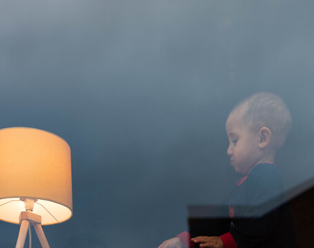 Portrait Of Boy Looking At Illuminated Lamp