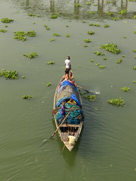 Rear View Of Man On Fishing Boat In River