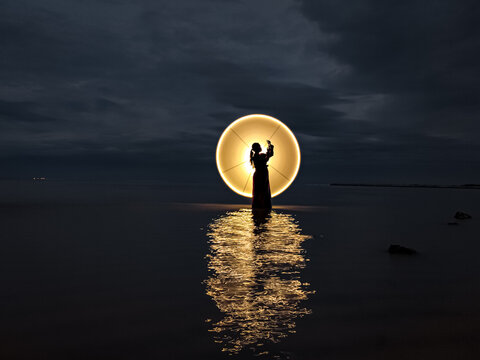 Illuminated Lamp On Sea Against Sky During Sunset