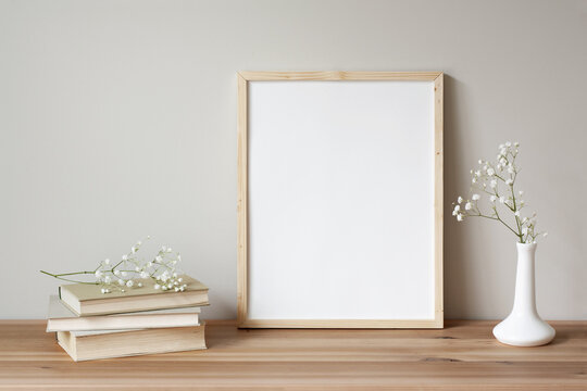 11x14 thin wood vertical frame mockup for art and quotes. Vintage stack of books and flowers as props.