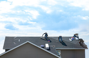 Obraz 4 construction workers fixing roof against clouds blue sky, install shingles at the top of the house. Renovate, improvement, build home exterior by professional teamwork. Safety and protection concept - fototapety do salonu