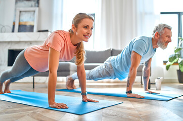 Fototapeta Sport, fitness and healthy lifestyle concept. Mature couple doing exercise or yoga at home. How to stay healthy in quarantine. obraz