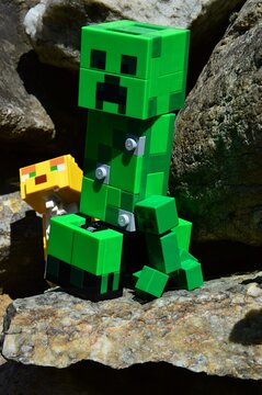 LEGO large figure of Creeper monster mob standing on rock, Ocelot cat predator looking from cave behind him. Spring afternoon sunshine.