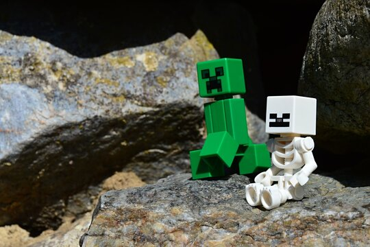 LEGO Minecraft monster mobs, Skeleton and Creeper, sitting in front of mountain cave in spring afternoon sunshine.