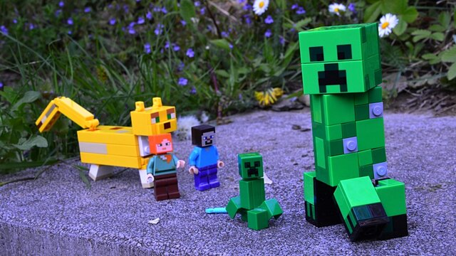 LEGO Minecraft figures of Steve and Alex chasing small and large creepers with large Ocelot cat animal on stone block in spring garden.