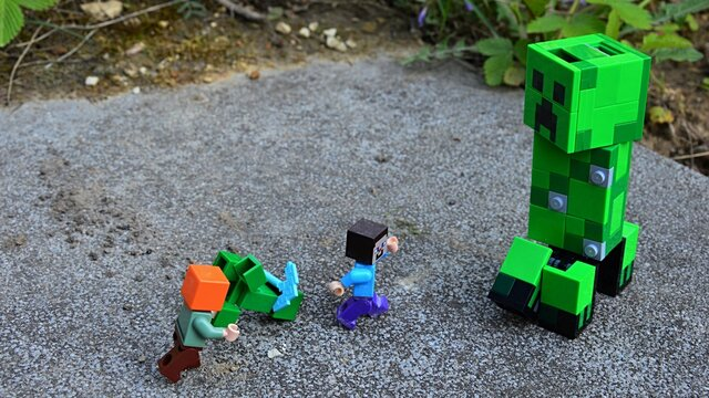 LEGO Minecraft figures of Steve and Alex, fighting with small green Creeper monster mob on large stone block in garden, large figure of Creeper is watching.
