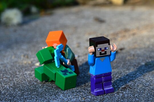 LEGO Minecraft Steve figure running from Alex with diamond pickaxe fighting with explosive green Creeper mob monster on large stone block.