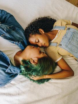 Pareja de jóvenes lesbianas toma un descanso en la cama de su habitación