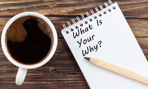 WHAT'S YOUR WHY text on notebook with coffee on wooden background