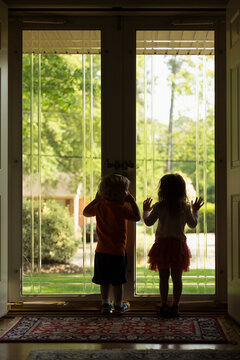 Male and female toddler friends silhouetted by patio door