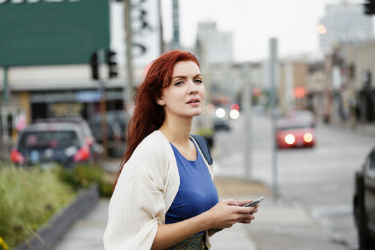 Young woman with long red hair, using smartphone in street