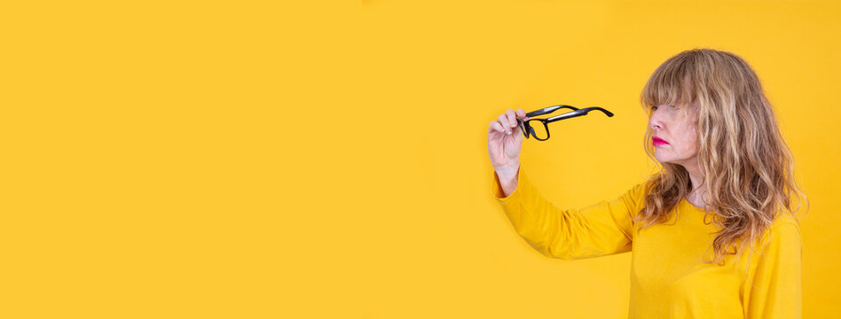 Woman has vision problems, squints her eyes while trying to see something, takes off her glasses, isolated on yellow background. Myopia, hyperopia, vision concept. See Less