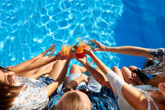 Top view of of friends clinking glasses with fresh colorful cocktails sitting by swimming pool on sunny summer day. People toast drinking beverages at luxury villa poolside party on tropical vacation.