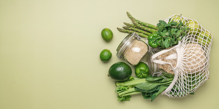 Green vegetables and fruits in mesh bag on pastel green background. Local, farm, organic food. Plastic free shopping