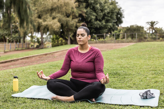 Curvy woman doing yoga session outdoor at city park - Focus on face