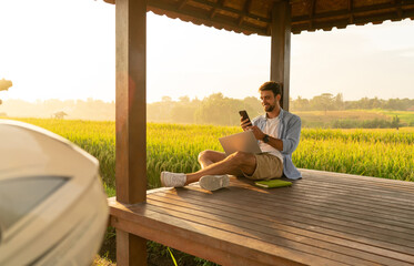 Positive young guy chilling in field gazebo with smartphone and laptop