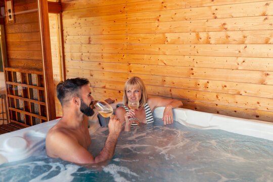 Couple drinking wine in a hot tub