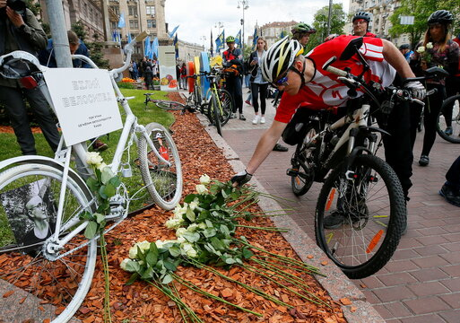 Cyclists take part in a commemoration ceremony for their colleague who was hit by a car, during a protest in Kyiv