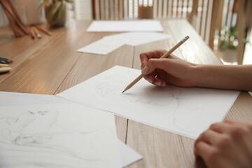 Fototapeta Young woman drawing male portrait at table indoors, closeup obraz
