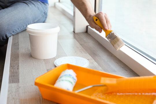Man painting window frame at home, closeup