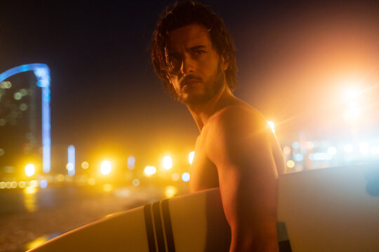 Night portrait of young handsome man, surfer holding surf board and looking away, ready for surfing at Barcelona beach