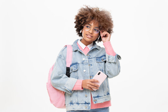 African american school girl with afro hairstyle, pink backpack and trendy round glasses holding phone, looking away, isolated on gray background