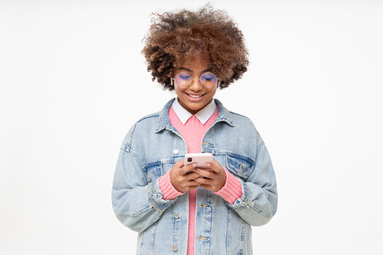 African american teenage girl with afro hairstyle holding smartphone with both hands, chatting with friend, smiling, using social media app, isolated on gray background