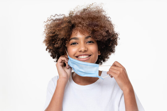 Smiling african american school girl taking off face mask after the end of pandemic. Concept of future, hope and recovery. Covid virus defeated, people are getting back to normal life