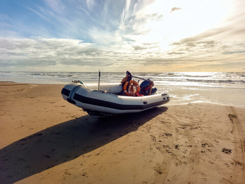 Rigid hull inflatable boat with outboard motor in the shore beaten by the waves. Used to fish at sea