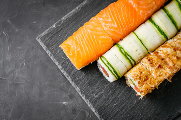 Fototapeta appetizing set of sushi roll on a black stone plate obraz