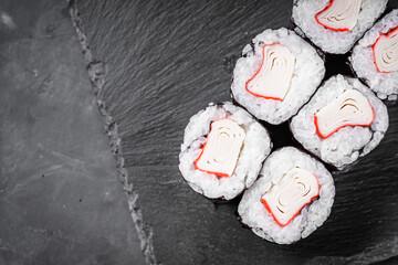 Fototapeta appetizing sushi roll maki with crab stick on a black stone plate obraz