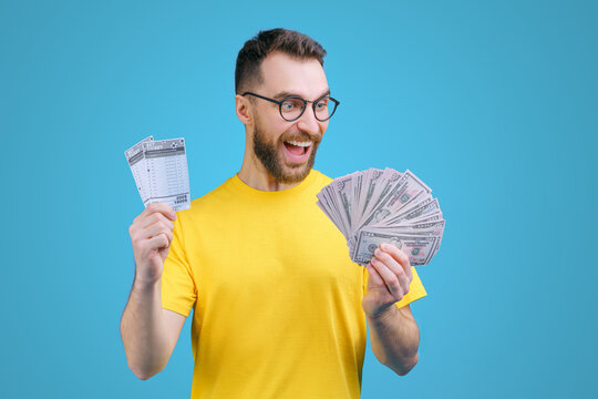 Portrait of happy euphoric bearded man in yellow t-shirt posing with lottery ticket and ward of dollar bancknotes in hands as betting, gambling, money win concept