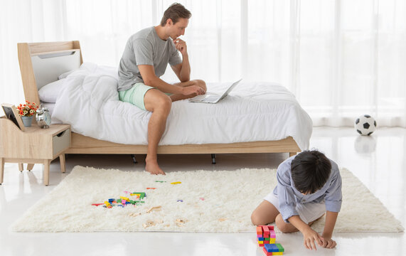 Father sitting on bed and working with notebook computer while his mixed-race son playing colorful wooden block in home bedroom. Idea for lifestyle of working from hom