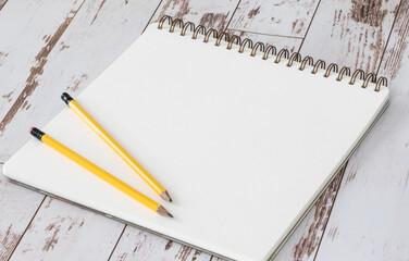Crayons de bois à mine de plomb déposés sur une feuille de papier blanche vide avec reliure en spirale sur surface de bois