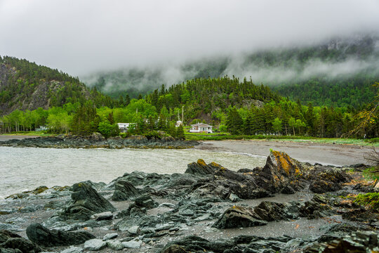 Rocky shore and view on l'Anse a Capelans in Parc National du Bic near Rimouski in Bas St Laurent (Quebec, Canada) on a rainy and moody day