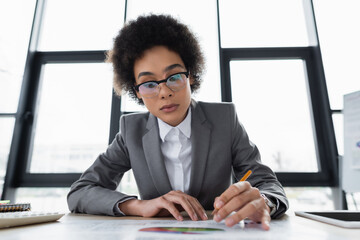 Obraz African american businesswoman with pencil working with document on blurred foreground - fototapety do salonu