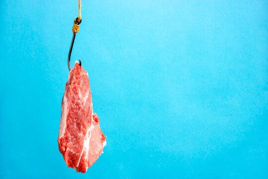 Raw meat on a hook. Raw pork steak. Hook bait.